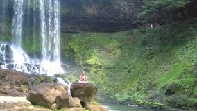 Kvinnan sitter i lotusblomma mot den branta Green River banken stock video