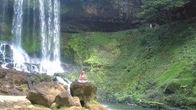 Kvinnan sitter i lotusblomma mot den branta Green River banken arkivfilmer