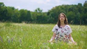 Kvinnan sitter i lotusblomma poserar att meditera utomhus, vind flyttar hår, enhetnatur stock video
