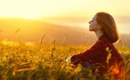 Kvinnan sitter med henne tillbaka i fält- och blicksolnedgången i mouen Royaltyfri Foto