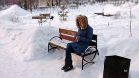 Kvinnan sitter på bänk, och bläddra mobiltelefonen i vinterstad parkera under dagen i snöig väder med att falla arkivfilmer