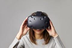 Kvinnan sitter på den Sofa At Home Wearing Virtual verklighethörlurar med mikrofon Arkivfoto