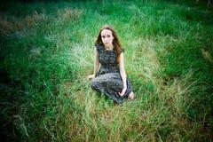 Kvinnan sitter på en äng arkivfoto