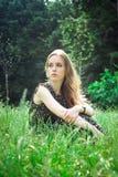 Kvinnan sitter på en skogs äng arkivbilder
