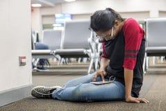 Kvinnan sitter på golv och laddar upp telefonen Arkivbild