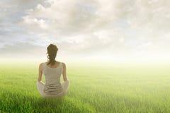 Kvinnan sitter på grässlätt Arkivfoton