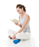 Kvinnan sitter på jordning och läste en bok royaltyfria foton
