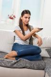 Kvinnan sitter på soffan med fjärrkontroll Arkivbild