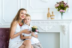 Kvinnan sitter på soffan med hennes son och dotter arkivfoton