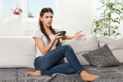 Kvinnan sitter på soffan med fjärrkontroll Royaltyfri Foto