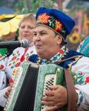 Kvinnan sjunger och spelar dragspelet, underhåller folk Arkivbilder