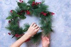 Kvinnan skapar den dekorativa kransen för grön jul Arkivbild