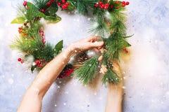 Kvinnan skapar den dekorativa kransen för grön jul Royaltyfri Foto