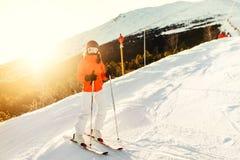 Kvinnan skidar på under vinter Flickaskidåkning i en bergsemesterort på lutningarna Arkivbilder