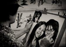Kvinnan skissar ett par av kvinnliga framsidor från ett fotografi royaltyfria bilder