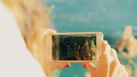 Kvinnan skjuter landskapvideoen med hennes smartphone på sjökusten på en solig dag Skjutit p? R?D kamera arkivfilmer