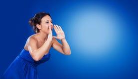 Kvinnan skriker framme av en blå backround royaltyfri bild