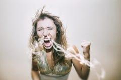 Kvinnan skriker och svär en rök från hans näsa i en passform av emotien fotografering för bildbyråer