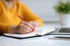 Kvinnan skriver anmärkningar på en dagbok Arkivfoto