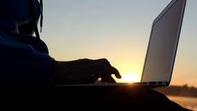 Kvinnan skriver en saga på en sjöbank i slo-mo stock video