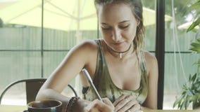 Kvinnan skriver i anteckningsbok i mysigt kafé arkivfilmer