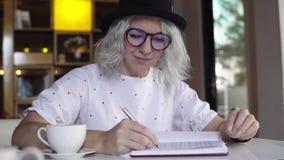 Kvinnan skriver i dagbok lager videofilmer
