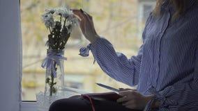 Kvinnan skriver i dagboksammanträdet på fönsterfönsterbräda lager videofilmer