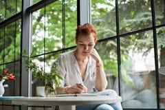Kvinnan skriver i en anteckningsbok Fotografering för Bildbyråer