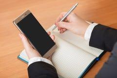 Kvinnan skriver i en anteckningsbok Arkivbild