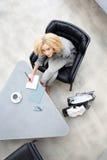 Kvinnan skriver i en anteckningsbok Arkivfoto