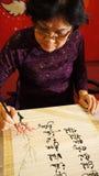 Kvinnan skriver kalligrafi Arkivbild