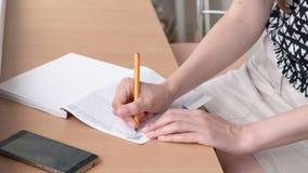 Kvinnan skriver något i anteckningsboken som hemma sitiing på balkongen Händer för närbildkvinna` s stock video