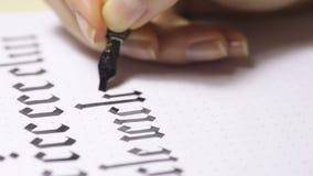 Kvinnan skriver pennan med calligraphic bokstäver stock video