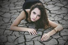 Kvinnan skyddar en liten grodd på en sprucken ökenjord