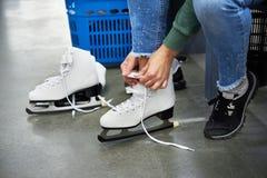 Kvinnan snör åt diagramet skridskor i sportar shoppar Arkivbilder
