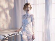 Kvinnan snör åt in klänningen på fönstret Arkivfoto