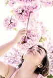 Kvinnan sniffar filialen av sakura, blått filter arkivbilder