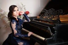 Kvinnan snör åt in den djupblå klänningen som spelar pianot för stilvektor för illustration retro tappning Royaltyfri Bild