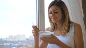Kvinnan som äter sädesslag med, mjölkar ut ur bunkeanseende på fönstret och att se utanför arkivfoto