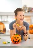 Kvinnan som äter trick- eller festgodisen i halloween, dekorerade kök arkivbild