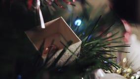 Kvinnan som öppnar en julgåva och där, är en vigselring på ett julträd arkivfilmer