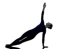 Kvinnan som övar den Vasisthasana sidoplankan, poserar yogakonturn Arkivbild