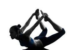 Kvinnan som övar yogabowen, poserar Arkivbild