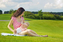 Kvinnan som ammar henne, behandla som ett barn utomhus Arkivfoton