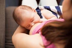 Kvinnan som ammar hennes nyfött, behandla som ett barn Royaltyfria Foton