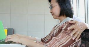 Kvinnan som använder bärbara datorn, man sätter armen på hennes skuldra