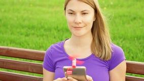 Kvinnan som använder den bärbara ventilatorn på mobiltelefonen parkerar in, under värme Kyla ner med den lilla fanen lager videofilmer