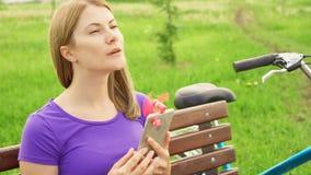 Kvinnan som använder den bärbara ventilatorn på mobiltelefonen parkerar in, under värme Kyla ner med den lilla fanen arkivfilmer