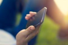 Kvinnan som använder den smarta telefonen för mobilen i hand, kopplar av på parkera arkivfoton