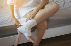 Kvinnan som använder resår, förbinder med benet, kvinnligt sätta förbinder på hans sårade ankel royaltyfria bilder
